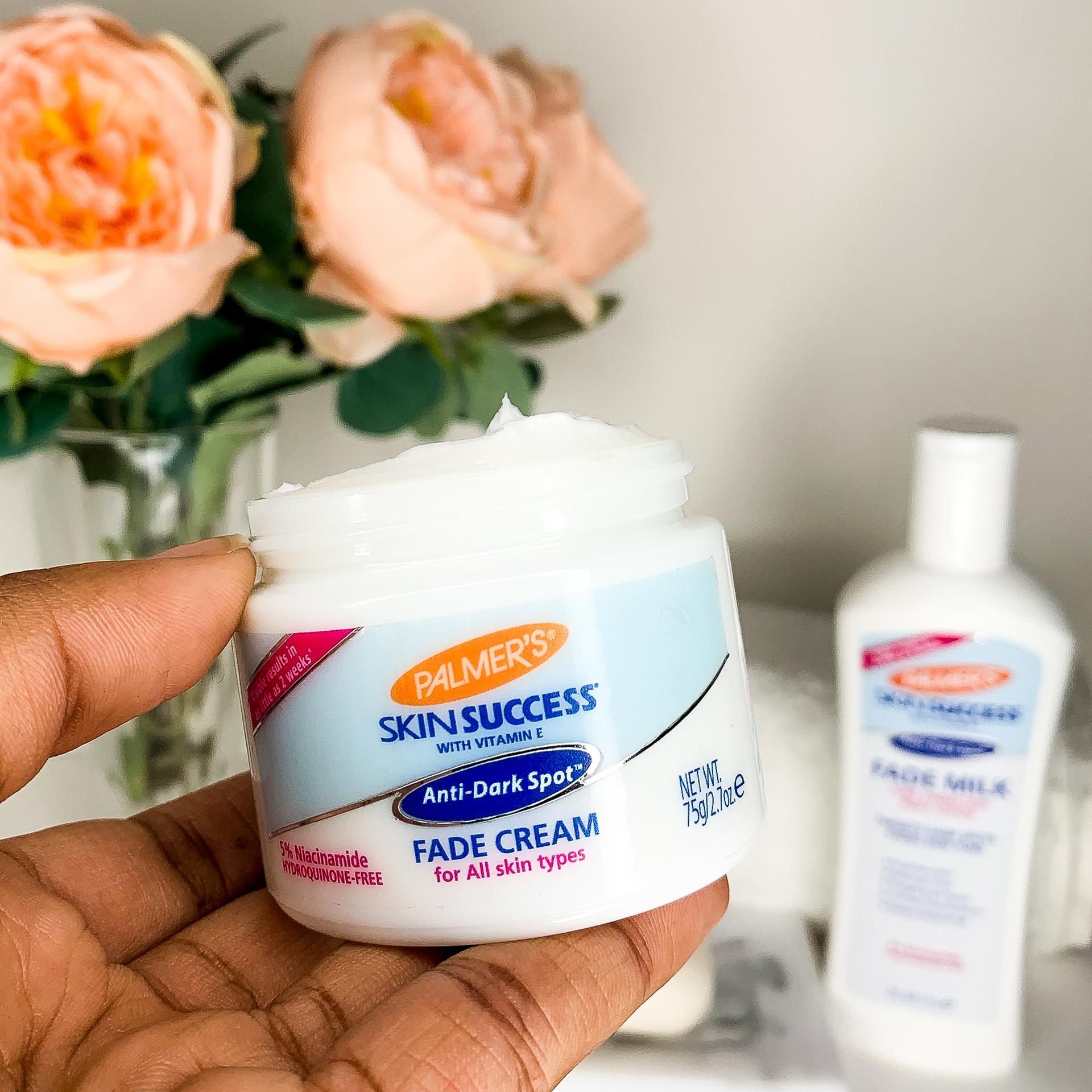 Palmer's Skin Success Anti-Dark Spot Fade Cream, an anti-aging cream with retinol and niacinamide, held in hand