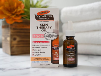 Palmer's Cocoa Butter Formula Skin Therapy Face Oil, a face oil for dry skin, on counter with flowers and towels