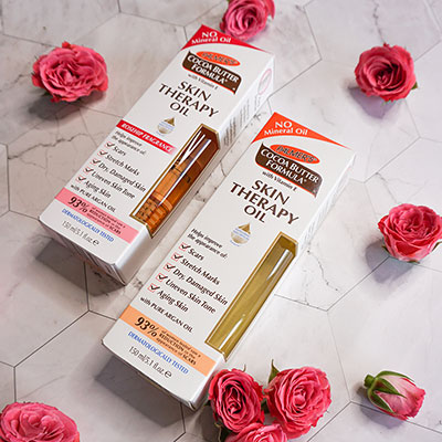 Palmer's Skin Therapy Oil and Skin Therapy Oil Rosehip, the best body oils for dry skin, on a table with roses