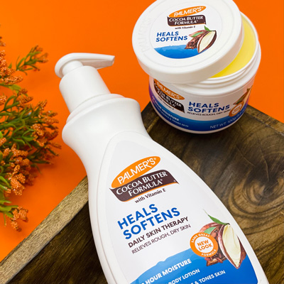 Palmer's Cocoa Butter Formula Daily Skin Therapy Body Lotion and Original Solid Jar, the best moisturizers for all skin types, on wooden plank with orange background