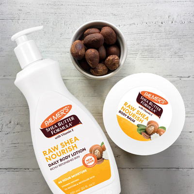 Palmer's Shea Butter Formula Shea Nourish Body Lotion and Body Balm, one of the best moisturizers for all skin types, on a wooden table with shea nuts