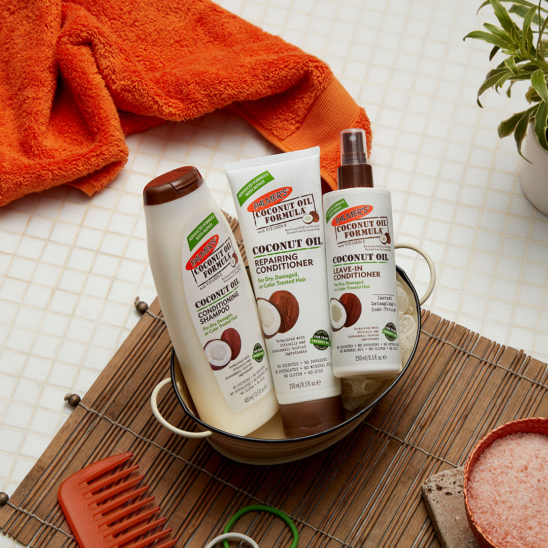 Palmer's Coconut Oil Formula Shampoo, Conditioner and Leave In in a bucket on a table