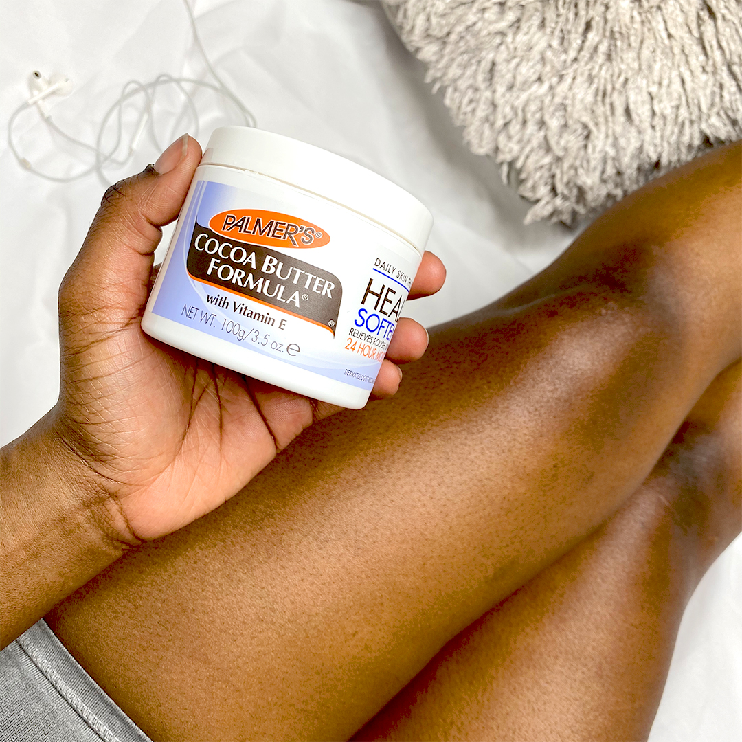 Palmer's Cocoa Butter for Dry Skin Original Solid Jar in woman's hand being held over legs