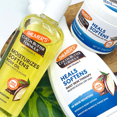 Palmer's Cocoa Butter Formula Moisturizing Body Oil, Body Lotion and Original Solid Jar on a table