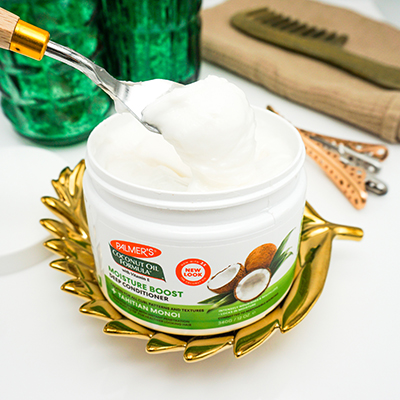 Palmer's Coconut Oil Formula Moisture Boost Deep Conditioner for healthy hair on table being scooped out of jar