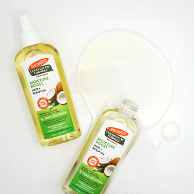 Palmer's Coconut Oil Formula Moisture Boost Hair and Scalp Oil for a healthy hair and scalp routine on table with oil spilled