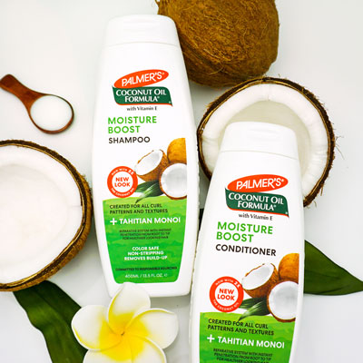 Palmer's Coconut Oil Formula Moisture Boost Shampoo and Conditioner for healthy a healthy hair routine on a table with coconuts