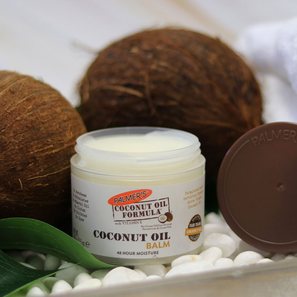 Palmer's Coconut Oil Balm, a solid coconut oil for feet product, on a table with coconuts