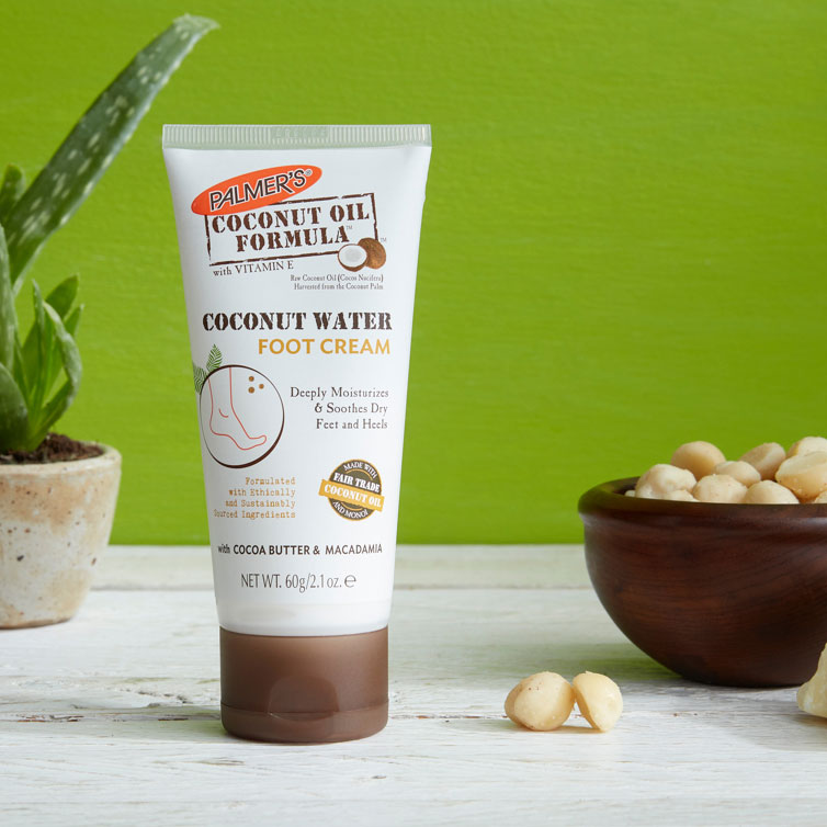 Palmer's Coconut Water Foot Cream, a coconut oil for feet product, on a table with macadamias