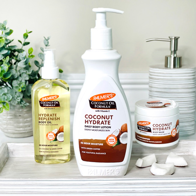 Palmer's Coconut Oil Formula with green coffee extract for skin on bathroom counter with coconut pieces