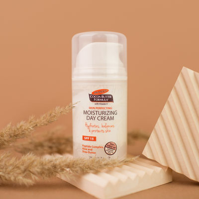 Palmer's Cocoa Butter Formula Moisturizing Day Cream, the perfect additional to your fall skincare routine, on table with ingredients