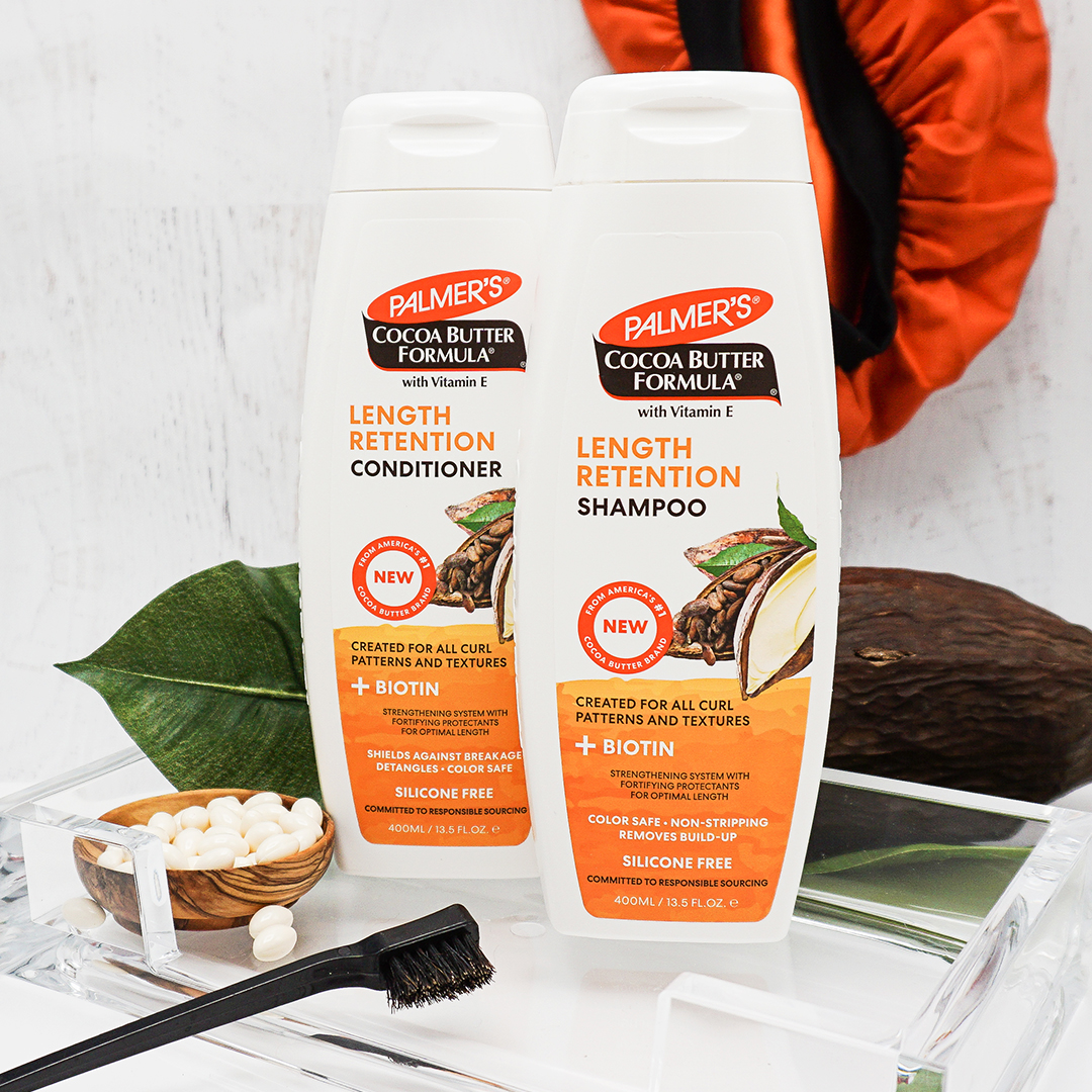 Palmer's Cocoa Butter Formula Shampoo and Conditioner with Biotin for repairing brittle or damaged hair on table with ingredients