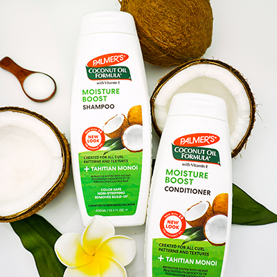 How to Keep Hair Moisturized in Summer with Palmer's Moisture Boost Shampoo and Conditioner on table with cracked open coconuts