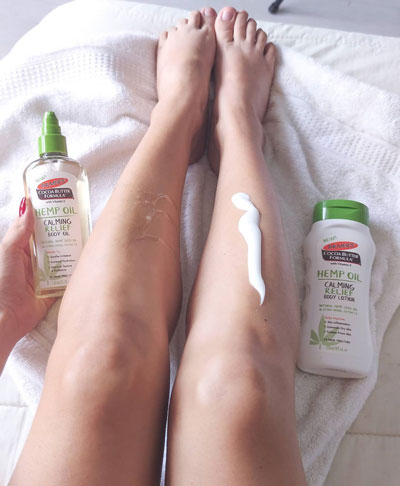 Palmer's Hemp Oil Calming Relief Body Lotion and Body Oil for moisturizing dry skin during winter being applied to legs