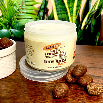 Palmer's Shea Formula Raw Shea Butter Balm, the best balm for sensitive dry skin on a table with shea nuts