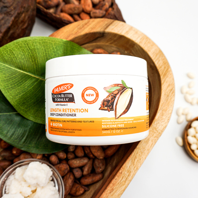 Palmer's Cocoa Butter Formula Length Retention Deep Conditioner for strengthening natural hair on table with cocoa beans