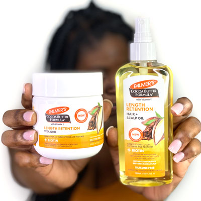 Black woman holding Palmer's Cocoa Butter Formula Length Retention for strengthening natural hair