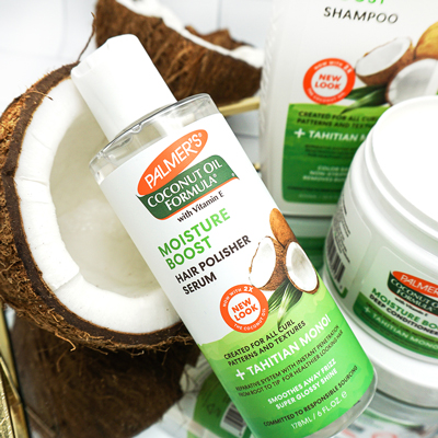 Palmer's Coconut Oil Moisture Boost Hair Polisher Serum for moisturizing dry natural hair on table with coconuts