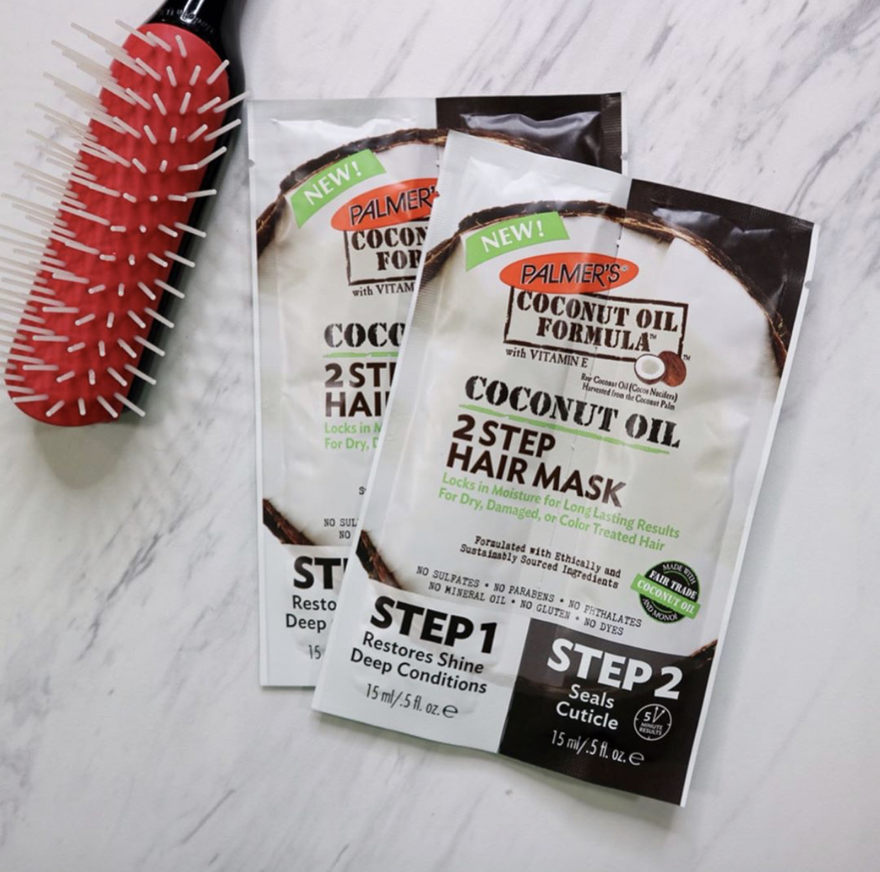 Palmer's Coconut Oil Formula 2 Step Hair Mask for dry hair on table with brush
