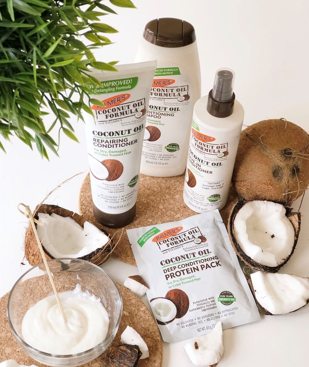 Palmer's Coconut Oil Formula Hair products for damaged hair on table with coconuts