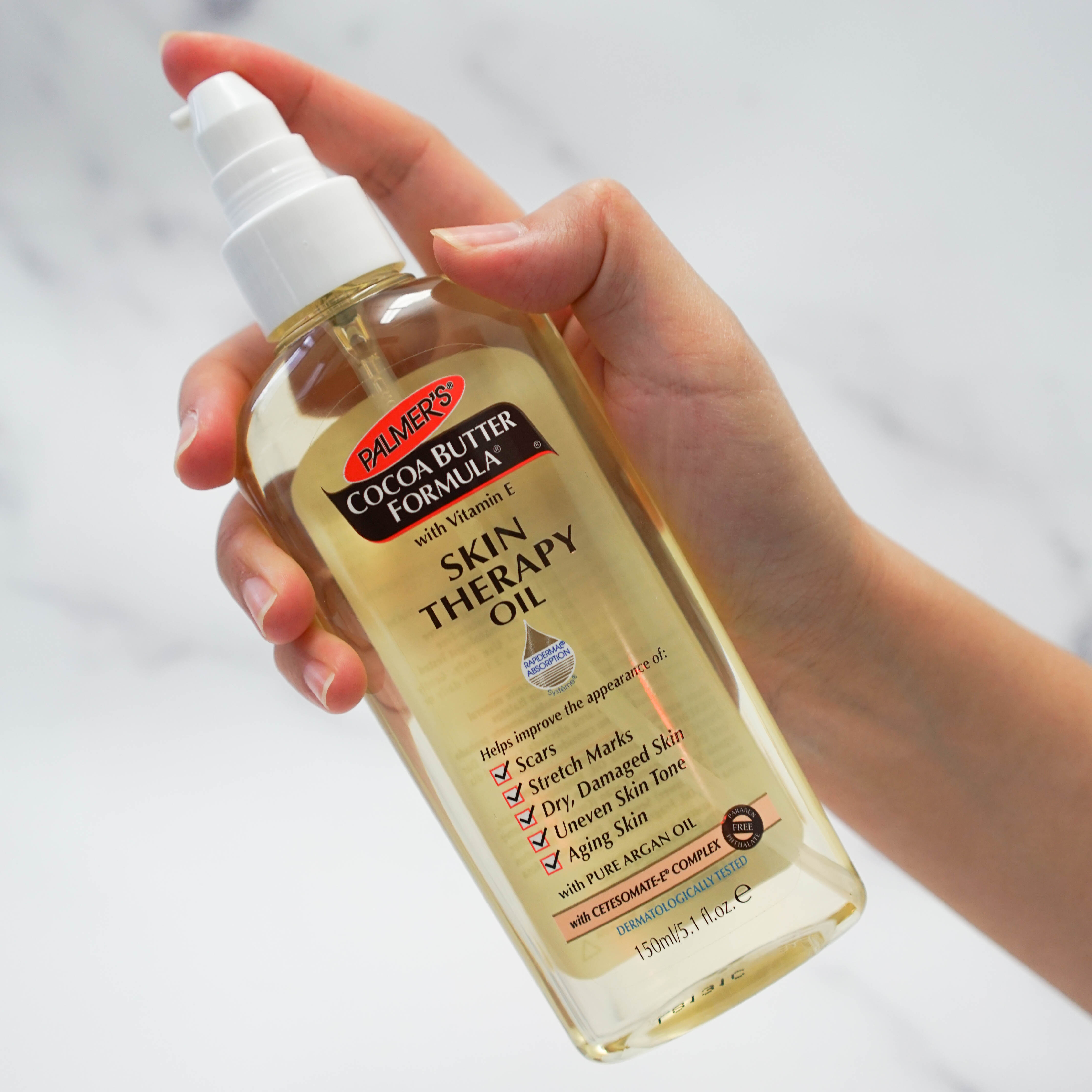 Palmer's Cocoa Butter Formula Skin Therapy Oil in hand