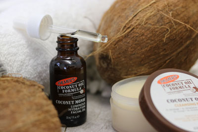 Palmer's Coconut Oil Facial Oil and Cleansing Balm, the best nighttime skin care routine for dry skin, on table with coconuts