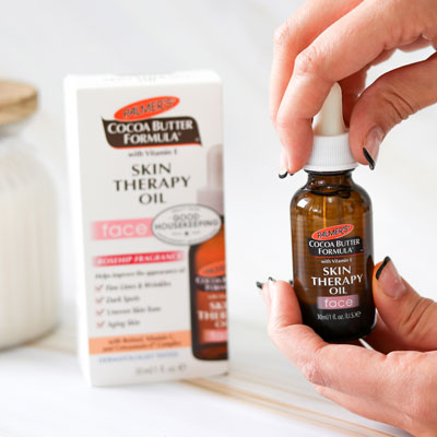Palmer's Skin Therapy Face Oil, the best nighttime skin care routine for aging skin, on table with hand holding dropper