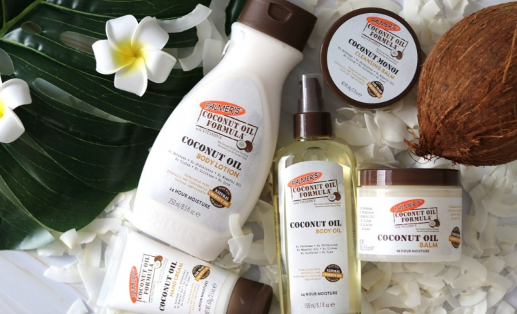 Palmer's Coconut Oil Formula skincare products on a table with coconuts and flowers