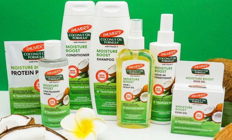 Palmer's Coconut Oil Formula Moisture Boost system, a coconut oil hair care routine for soft, healthy hair on a table with coconuts