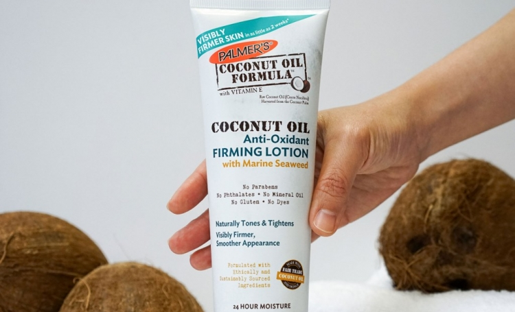 Palmer's Coconut Oil Formula Anti-Oxidant Firming Lotion being picked up from table