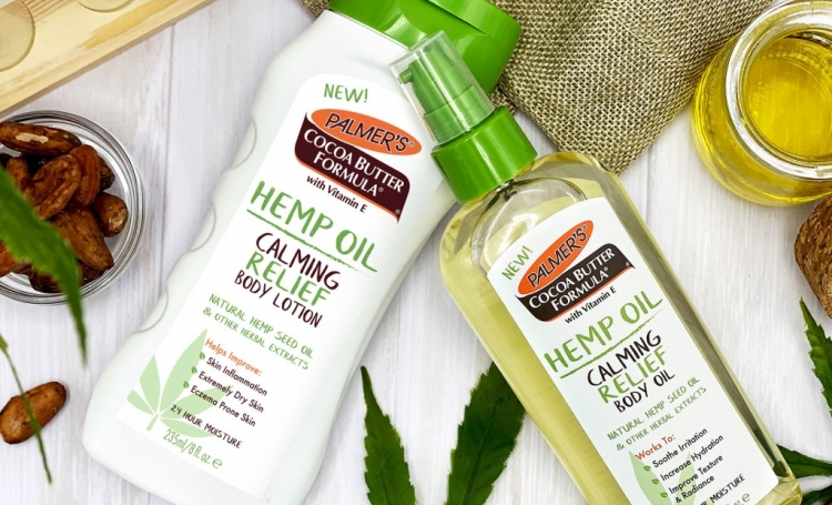 Palmer's Hemp Oil Body Lotion & Body Oil on table to cocoa beans and hemp oil and leaves