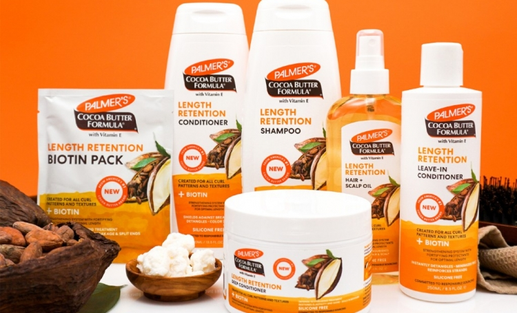 Palmer's Cocoa Butter Length Retention Hair Products on a table with ingredients against an orange background