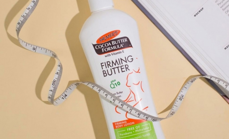Palmer's Firming Butter, skin care for after pregnancy, on a table with a book and measuring tape