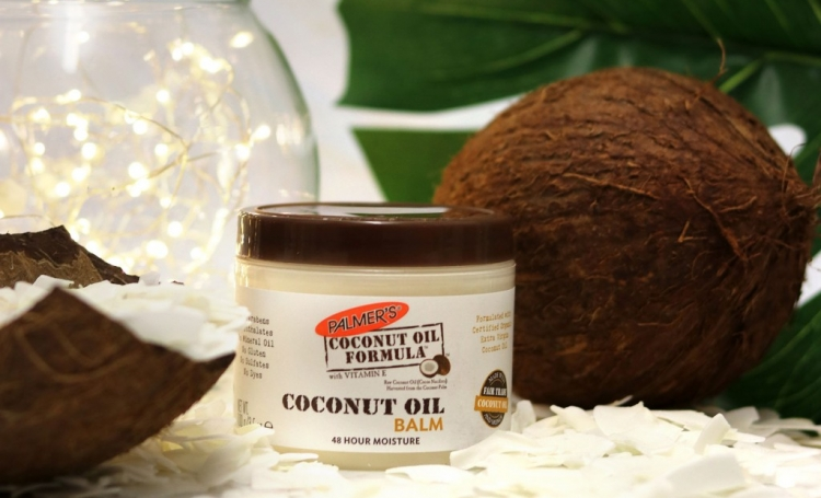 Palmer's Coconut Oil Balm, a dry skin balm, on a table with coconuts and coconut flakes