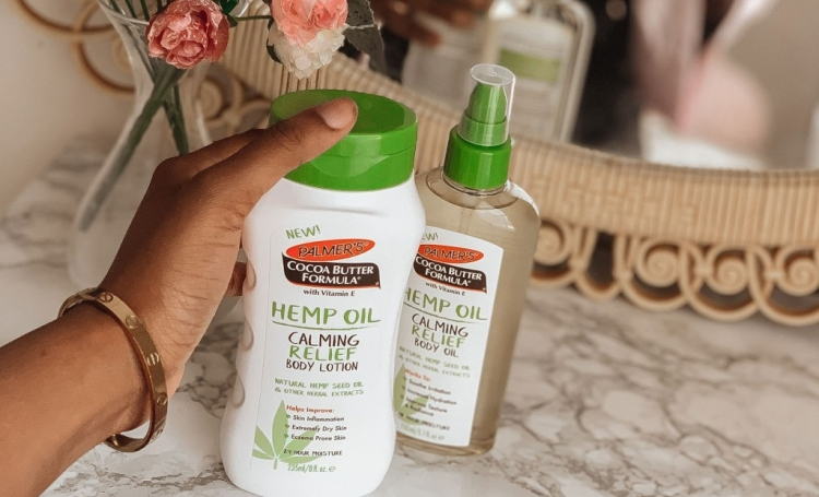 Hand grabbing Palmer's Hemp Oil Calming Relief Body Lotion to moisturize and care for dry skin in the winter